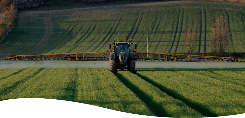 Tractor spraying crops in a field